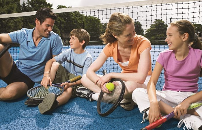 Family sitting on a tennis court