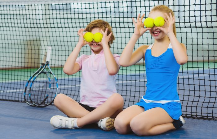 children having fun and playing on the tennis court.