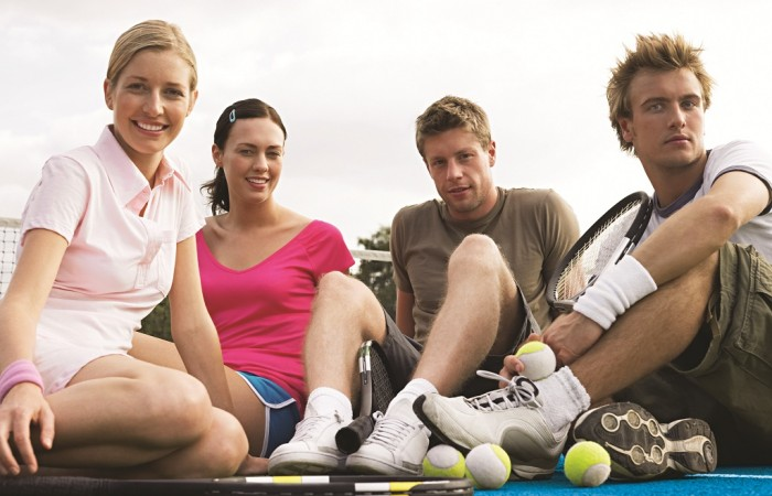 Friends sitting on a tennis court