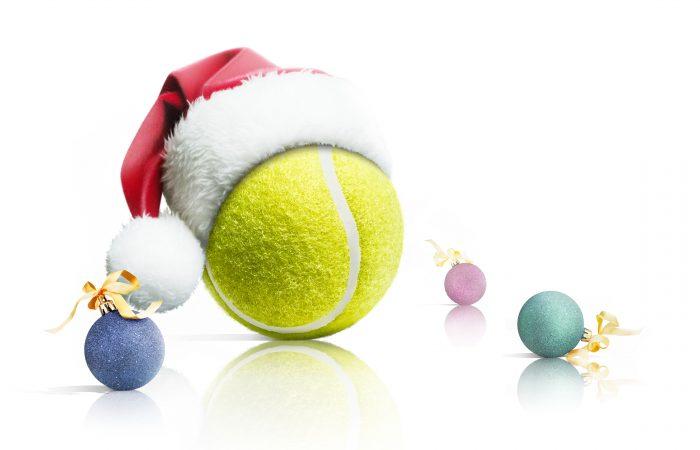 Christmas tennis. Tennis ball in Santa hat Christmas toys on white background.