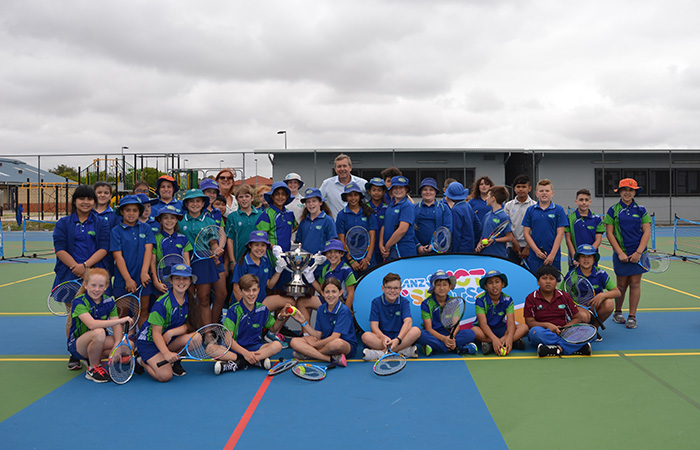 Yajat Sharma holds the Hopman Cup Trophy (standing with the Cup, top left) as part of Bertram Primary School's court resurfacing celebration made possible through Tennis Australia's National Court Rebate (NCR) scheme and joint fundraising efforts from the school community, local business and the Coles Community Challenge.