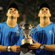 The Bryans look up as they hold their Australian Open 2011 trophy.