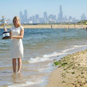 Clijsters at Brighton Beach with the city in the background as she holds her Australian Open 2011 trophy.