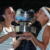 Flavia Pennetta and Gisela Dulko kiss their Australian Open 2011 women's doubles trophy.