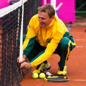 13th of April 2011. Dave Taylor dodges tennis balls while making a net adjustment ahead of the Australia v Ukraine Federation Cup tie. Mark Riedy.