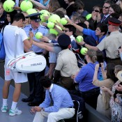 Look who's popular: Bernard Tomic signs autographs for his new fans after dispatching fifth seed Robin Soderling in the third round. GETTY IMAGES