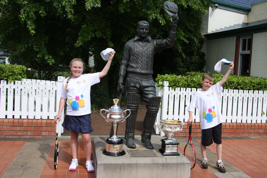 MLC Tennis Hot Shots kids with statue of Sir Donald Bradman. TENNIS AUSTRALIA