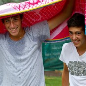 Daniel Guccione (L) and Thanasi Kokkinakis shelter beneath a towel during a cold and rainy Day 1 of the Junior Davis and Fed Cup Asia/Oceania qualifying competition in Bendigo; Tennis Australia