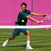 Bernard Tomic of Australia plays a volley during a practice session ahead of the 2012 London Olympic Games at Wimbledon; Getty Images