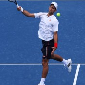 Novak Djokovic hits an unorthodox shot during his straight-set rout of Juan Martin del Potro in the Cincinnati semifinals, reversing the result of the pair's recent bronze medal match at the London 2012 Olympics; Getty Images