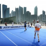 Janko Tipsarevic of Serbia returns a shot as doubles partner Nico Hulkenberg of the Force India Formula 1 racing team watches on in a match on a temporary court placed on Singapore's Marina Parade promenade during the ATP World Tour's promotion of its Asian swing; Getty Images for ATP