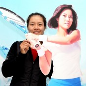 Na Li poses with a likeness of herself while visiting the Kunlun Mountains natural Mineral Waters booth during the China Open at the China National Tennis Center in Beijing, China; Getty Images