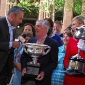 Ken Rosewall (centre) holds the Norman Brookes Challenge Cup as he is interviewed by Seven Sunrise's Mark Beretta in Sydney. Sunrise co-host Melissa Doyle (right) holds the Daphne Akhurst Memorial Cup; Tennis Australia