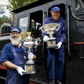 Puffing Billy train drivers Gary (L) and Les pose with the Australian Open trophies; Bek Johnson