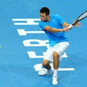 Bernard Tomic stretches for a backhand in his singles match against Andreas Seppi of Italy during Day 6 of the Hopman Cup at Perth Arena, a match he went on to win in straight sets; Getty Images