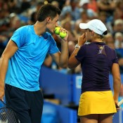 Aussies Bernard Tomic and Ashleigh Barty discuss tactics during their mixed doubles match against Novak Djokovic and Ana Ivanovic of Serbia, which they ultimately lost in an exciting third-set match tiebreak; Getty Images