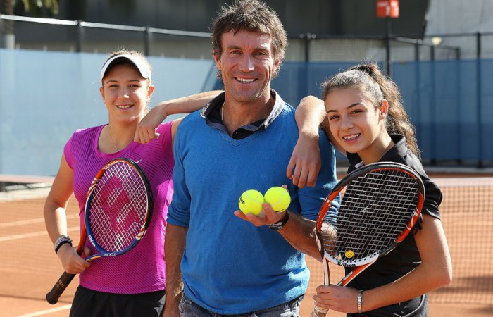 Pat Cash poses with 2012 Gallipoli Youth Cup winner Ellen Perez (L) and Sera Yavuzcan (R) at the clay courts at Melbourne Park's National Tennis Centre; Tennis Australia