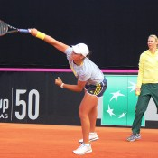 Ash Barty serves during a practice session, as captain Alicia Molik watches on, ahead of Australia's Fed Cup tie against Switzerland in Chiasso; Tennis Australia