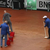 Ground staff mop the court after rain stopped play on Day 2 of the Fed Cup World Group Play-Off tie between Switzerland and Australia; Getty Images