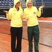 Jarmila Gajdosova (L) and Sam Stosur pose in the rain on Centre Court at Tennis Club Chiasso; Getty Images