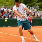 Bernard Tomic, slicing a backhand in his first round match against Victor Hanescu of Romania on Day 3 of the French Open, sustained a right hamstring injury early in the match; Getty Images