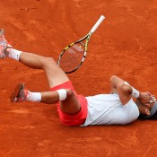 Rafael Nadal collapses to the court after dominating the men's singles final  against Spanish compatriot David Ferrer at Roland Garros in Paris, France. It was his eighth French Open title, and he becomes the first player in history to own more than seven titles at the one major tournament; Getty Images