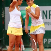 Aussies Casey Dellacqua (L) and Ashleigh Barty discuss tactics during their first round doubles loss to Mona Barthel of Germany and Liga Dekmeijere of Latvia; Getty Images