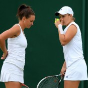 Casey Dellacqua (L) and Ash Barty discuss tactics during their opening round win over Valeria Solovyeva and Maryna Zanevska; Getty Images