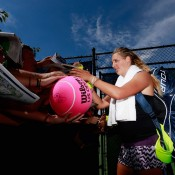 Victoria Azarenka of Belarus signs her autograph for fans following a practice session at the USTA Billie Jean King National Tennis Center in New York prior to the US Open; Getty Images for the USTA