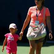 Mirka Federer leaves the practice courts with one of her children after watching her husband Roger Federer of Switzerland during a practice session ahead of the 2013 US Open; Getty Images