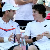John-Patrick Smith (R) talks with partner Paul Hanley during their 7-6(10) 7-6(4) first round men's doubles loss to Fabio Fognini of Italy and Albert Ramos of Spain at the 2013 US Open; Getty Images