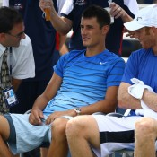 Bernard Tomic (centre) is attended to by a trainer during he and partner Chris Guccione's (R) second round match against Marcel Granollers and Marc Lopez of Spain at the 2013 US Open. Tomic was forced to retire when his team was up 2-1 in the opening set; Getty Images