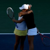Casey Dellacqua (L) and Ash Barty of Australia embrace after winning their US Open women's doubles semifinal against Sania Mirza of India and Jie Zheng of China; Getty Images