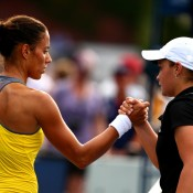 Ash Barty (R) shakes hands with Estrella Cabeza Candela after defeating the Spaniard 6-1 6-4 in the opening round of the US Open on Monday; Getty Images