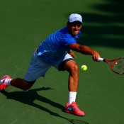 Bernard Tomic stretches for a backhand during his second round match against Daniel Evans of Great Britain on Day 4 of the 2013 US Open at Flushing Meadows; Getty Images