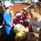 Sam Stosur (R) signs autographs after conducting a tennis clinic in Sofia, Bulgaria; WTA