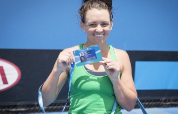 Casey Dellacqua poses with her Australian Open player accreditation after winning the Australian Open Play-off final over Arina Rodionova; Emily Mogic