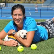 MELBOURNE, AUSTRALIA - JANUARY 19:  Garbine Muguruza of Spain cuddles 8 week old Remi, a puppy in training for Guide Dogs Victoria during day 7 of the 2014 Australian Open at Melbourne Park on January 19, 2014 in Melbourne, Australia.  (Photo by Vince Caligiuri/Getty Images)