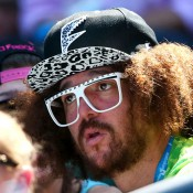 Singer Stefan Gordy, aka Redfoo watches Victoria Azarenka of Belarus in her first round match against Johanna Larsson of Sweden during day two of the 2014 Australian Open at Melbourne Park on January 14, 2014 in Melbourne, Australia.  (Photo by Scott Barbour/Getty Images)