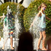 A young tennis fan cools off in a fountain as Melbourne heads towards 43 degrees celsius (109 degrees fahrenheit) during day two of the 2014 Australian Open at Melbourne Park on January 14, 2014 in Melbourne, Australia.  (Photo by Robert Prezioso/Getty Images)