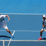 MELBOURNE, AUSTRALIA - JANUARY 17:  Chris Guccione of Australia and Thanasi Kokkinakis of Australia in action in their first round doubles match against Ivan Dodig of Croatia and Marcelo Melo of Brazil during day five of the 2014 Australian Open at Melbourne Park on January 17, 2014 in Melbourne, Australia.  (Photo by Cameron Spencer/Getty Images)