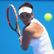 Casey Dellacqua of Australia plays a backhand in her first round match against Vera Zvonareva of Russia  during day one of the 2014 Australian Open at Melbourne Park on January 13, 2014 in Melbourne, Australia.  (Photo by Chris Hyde/Getty Images)