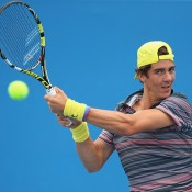 Thanasi Kokkinakis of Australia plays a backhand in his match against Di Wu of China during day two of the 2014 Brisbane International at Queensland Tennis Centre on December 30, 2013 in Brisbane, Australia.  (Photo by Chris Hyde/Getty Images)