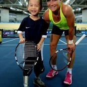 HONG KONG - MARCH 03:  Samantha Stosur of Australia poses for photographs with a child during a clinic ahead of the BNP Paribas Showndown at the Hong Kong Velodrome on March 3, 2014 in Hong Kong, Hong Kong.  (Photo by Stanley Chou/Getty Images)