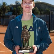 Jake Delaney holds the trophy after winning the final of the Gallipoli Youth Cup at Melbourne Park over Cormac Clissold; Elizabeth Xue-Bai
