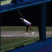 A reflection of Naiktha Bains of Australia serving seen in a window during her girls' doubles second round match with Tornado Alicia Black of the United States against Freya Christie and Isabelle Wallace of Great Britain on Day 10 at Wimbledon; Jan Kruger/Getty Images