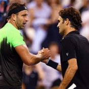 Marinko Matosevic (L) shakes hands with Roger Federer after his first round loss on Arthur Ashe Stadium at the Open; Getty Images