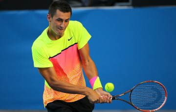 Bernard Tomic plays a backhand in his third round match against during day five of the 2015 Australian Open at Melbourne Park on January 23, 2015 in Melbourne, Australia.