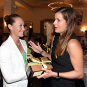 Sam Stosur (L) and Julia Goerges exchange gifts at the Fed Cup official team dinner; Paul Zimmer/ITF
