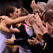 Andrea Petkovic (L) hugs her German teammates after defeating Sam Stosur 12-10 in the third set of their Fed Cup singles rubber in Stuttgart; Getty Images